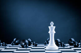 White Chess King among lying down black pawns on chessboard stock photo